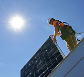 Crew member from Altenergy Inc. installs a solar panel