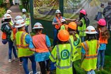 Several girls attend a tour of the Memorial for Enslaved Laborers construction zone during Girls Day 2019