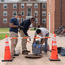 Facilities Management workers draw wastewater from a manhole near a UVA dorm