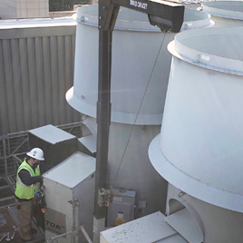 An FM employee services air handlers on the roof of a building
