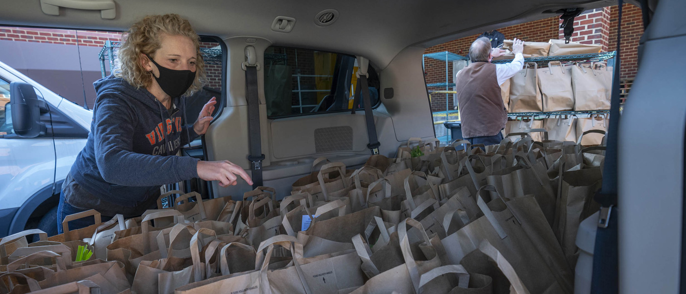 An FM employee takes stock of a van full of grocery bags