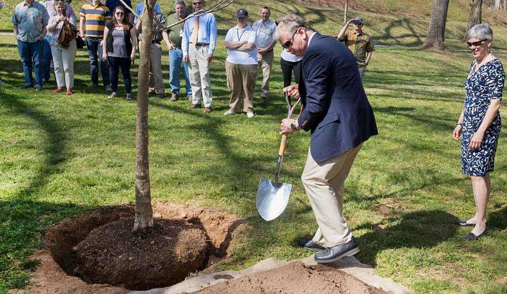 Jeff Sitler plants a tree as part of the annual Founder's Day ceremony