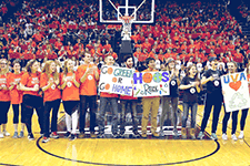Student volunteers holding sustainability posters line up on basketball court