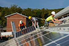 Workers install solar panel system on Leake II roof