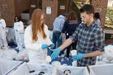 Engineering students sort through trash during a waste stream inventory