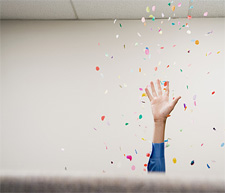 A woman tossing confetti in an office
