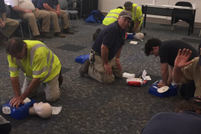 Facilities Management employees practicing CPR on dummies