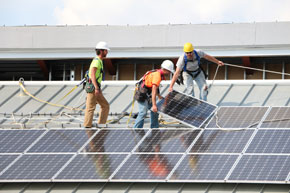 Crew installing solar panels on roof