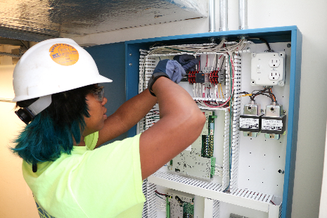 Rona Rose working on an electrical panel