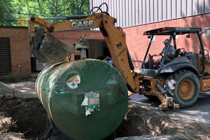 An underground storage tank being dug out by a backhoe operator