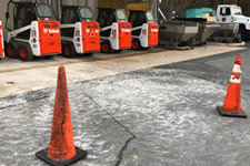 Safety cones and Bobcats parked in a row